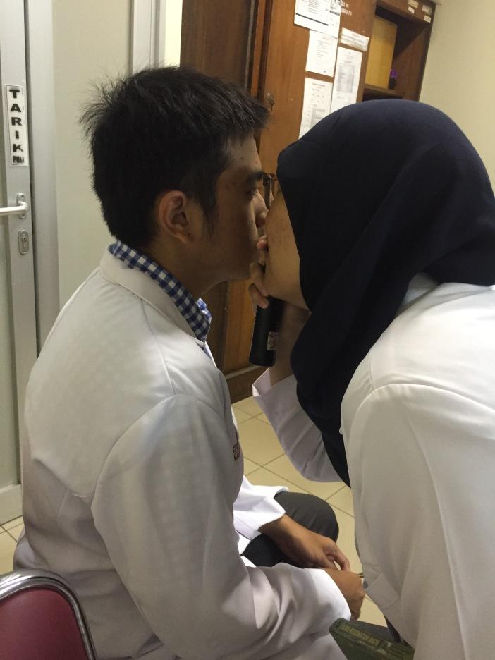 Kemesraan Nisa dan Bayu :3 just kidding. Ini waktu Nisa lagi coba meriksa mata Bayu pakai opthhalmoscope. ;)